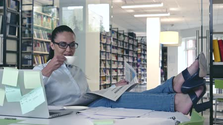 biblioteca : Smiling businesswoman with newspaper in office Stock Footage