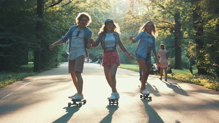 patim : Young people skateboarding in the summer park
