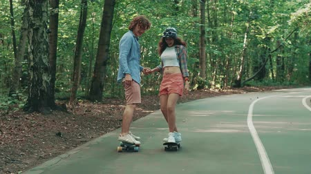 longboard : Young couple skateboarding outdoors