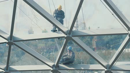 work at height : Builders on a glass roof Stock Footage