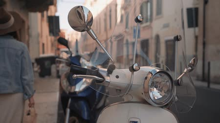 mobilet : Girl walking near a motorbike on the italian street