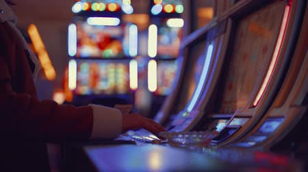 ギャンブル : Young girl playing at the casino machines indoors