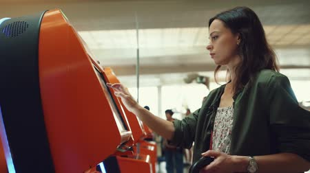 ticket machine : Attractive girl buying a ticket at the airport Stock Footage