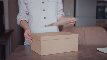 カートン : Young girl unpacking a parcel 動画素材