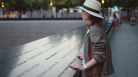 eleven people : Young woman in the park at the 911 Memorial