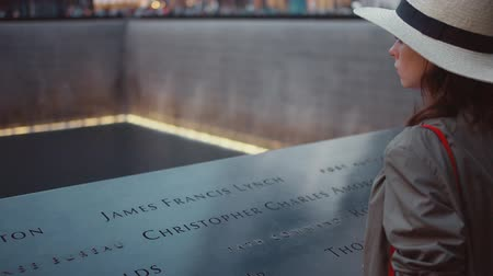 eleven people : Young girl in a hat at the 911 Memorial