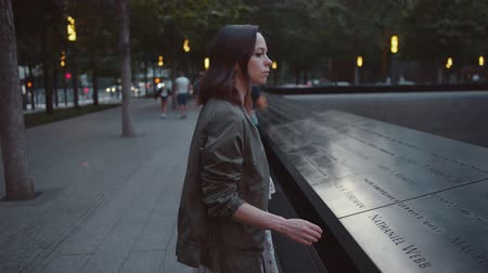 eleven people : Young woman at the 911 memorial with the names of the dead Stock Footage