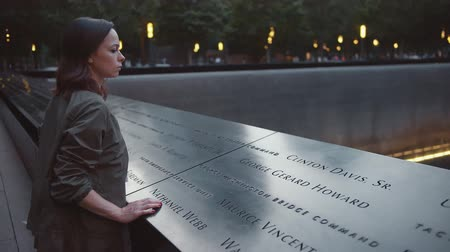 eleven people : Young woman at the 911 Memorial in the evening