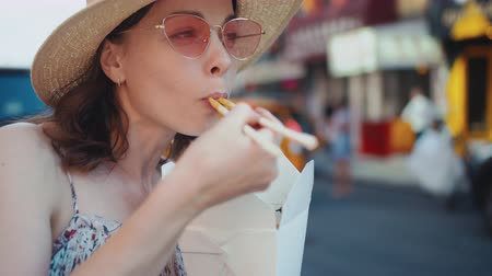 лапша : Young woman eating asian food in Manhattan in New York City