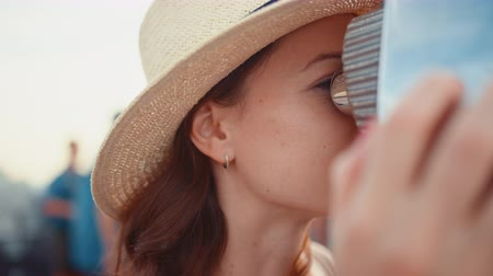 new york city : Attractive girl looking through binoculars at the view point