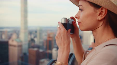 на камеру : Beautiful girl with a retro camera at the view point in New York