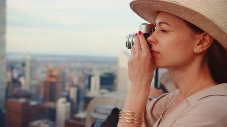 ニューヨーク : Young woman with a retro camera at the view point in New York