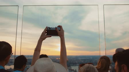body building : Young woman in the crowd taking a photo of sunset, NYC