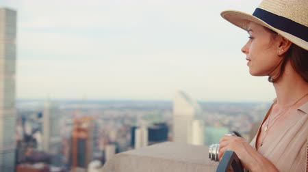 ニューヨーク : Young woman with a retro camera on the roof of New York skyscraper