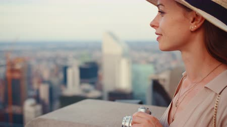 york : Attractive girl with a retro camera on the roof of New York skyscraper Stock Footage