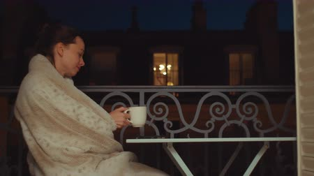 çay : Young girl with a cup of tea on a balcony in Paris Stok Video