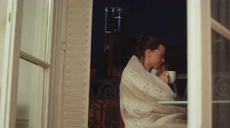 Young woman drinking tea on the balcony at night Dostupné videozáznamy