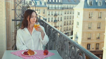 Smiling woman on a balcony in France in the morning Stock Footage