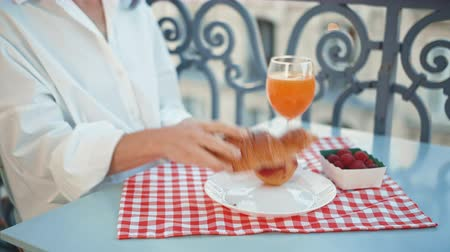 Young girl having breakfast outdoors in the morning Stock Footage