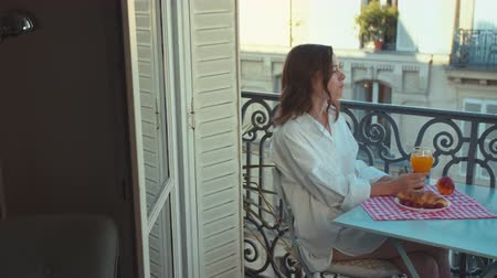 Beautiful woman having breakfast on a balcony in Paris