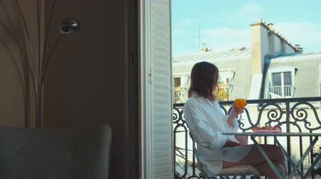 Attractive girl having breakfast on a balcony in France