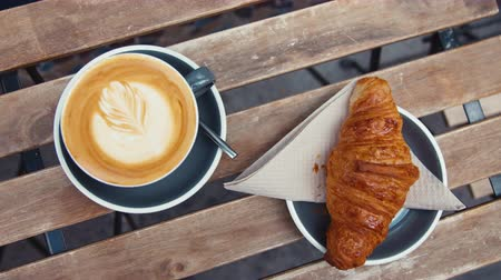 parigi : Breakfast of coffee and a croissant on a wooden table, close-up Filmati Stock