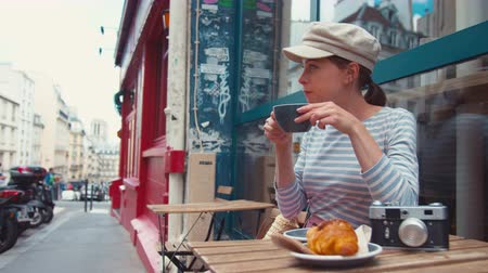 Young attractive girl having breakfast in a cafe in Paris Stock Footage