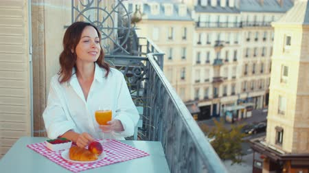 Attractive woman in a white shirt having breakfast on the balcony