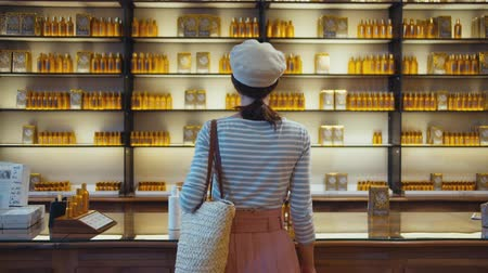 Young girl at the shelves with perfume in a french store