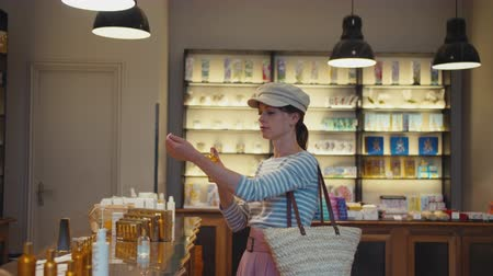 tüketici : Young woman with a vial of perfume in a shop, Paris