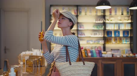 tüketici : Beautiful girl choosing a perfume in the shop