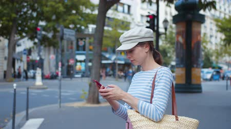 Young tourist with a smartphone on a street in Paris Filmati Stock