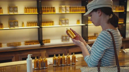 Beautiful girl choosing a perfume in a store in Paris
