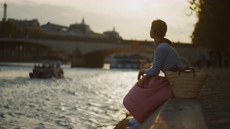Young girl by the river in Paris, France Stock Footage