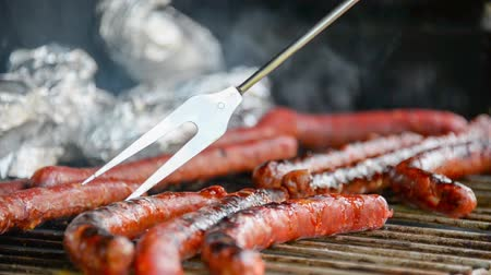 prepaid : Seamless loop - Fork turning over tasty juicy sausages grilling on a barbecue with potatoes in foil, HD video