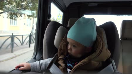 ülés : Baby boy sits in car on chair by city streets