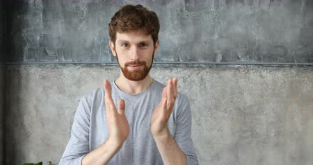 irony : caucasian guy with red hair applauds. handsome redheaded men wearing in casual t-shirt. Portrait ginger young caucasian man clapping hands on grey background Stock Footage