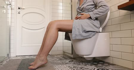 żołądek : Brunette woman sitting on toilet in the bathroom. She is holding her stomach. Wears a grey dressing-gown