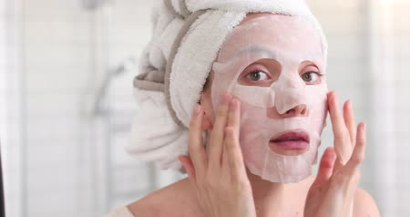 sheet : Woman applying cosmetic Japanese mask on her face and looking in the mirror looking at camera in the bathroom