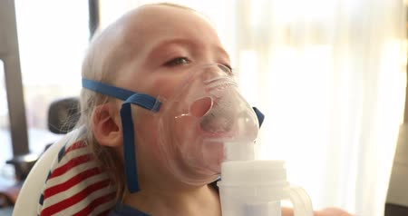 wheeze : Baby crying and wear oxygen mask. Boy cries in the mask of the inhaler close-up