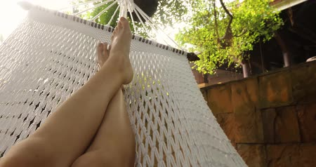 гамак : Crop shot of barefoot feet lying in white hammock and lounging in backyard. Стоковые видеозаписи