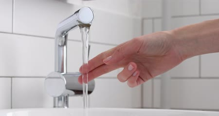 lavatório : Female hand opening silver faucet or water tap with white washing sink in toilet