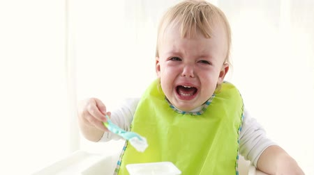 nepořádek : Little baby boy is upset, holding spoon with dairy. The young child is visibly sad. Kid does not want to eat sitting on a high chair Dostupné videozáznamy