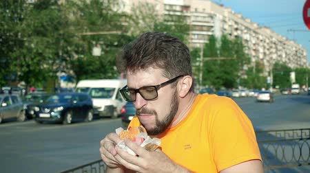 nezdravý : Bearded man greedily eating stale tasteless hamburger lunch break. Spits down
