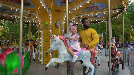 going round : Mom, dad and little daughter are going on a merry-go-round