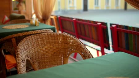 nem városi színhely : Wicker chair in an empty cafe. The camera moves Stock mozgókép