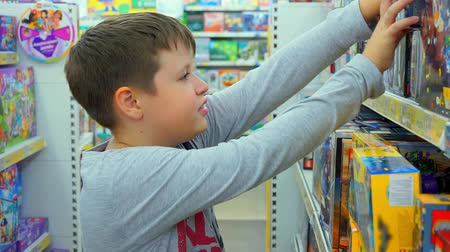 heroes : Boy 10-12 years chooses toys. Childrens toy store