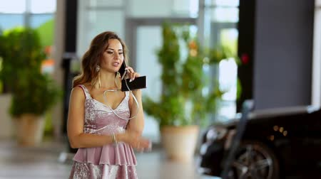 árverés : Attractive young woman buying car at the dealership.