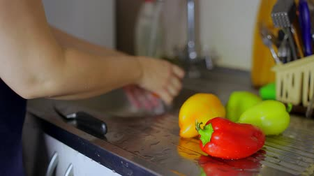 fresh produce : Hands housewives women wash peppers under a tap. Camera slide right