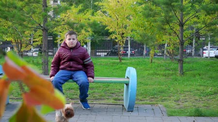 kidnapping : Boy sitting in the Park on a bench. Hes lost, waiting for his parents. Slow mo
